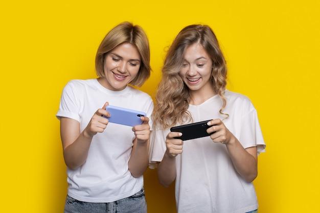 Twee blonde vrouwen met witte t-shirts spelen mobiele games op de telefoon die op een gele muur poseert