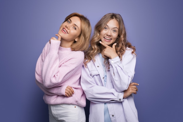 Twee blonde zussen poseren in dezelfde modieuze kleding en glimlachen vrolijk