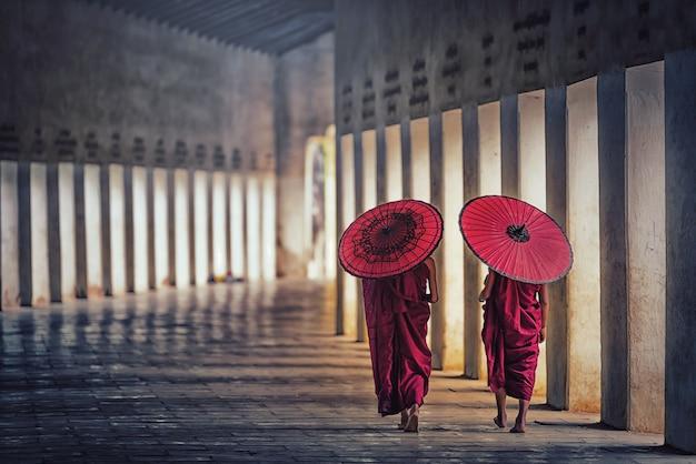 Twee boeddhistische monniksbeginneling die rode paraplu's houdt en in pagode, myanmar loopt.
