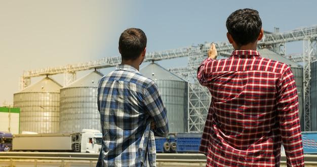 Twee boeren tegen graansilo's. landbouwbedrijf