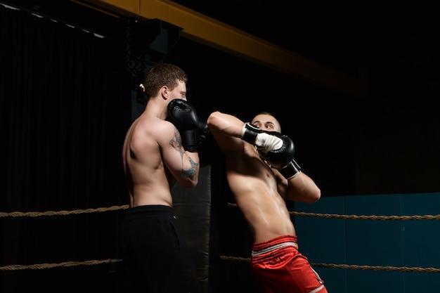 Twee boksers die vechten in boksring: man met getatoeëerde schouders staande in verdedigingspositie terwijl zijn tegenstander in rode broek elleboog op zijn gezicht richt. rivaliteit, confrontatie en competitie