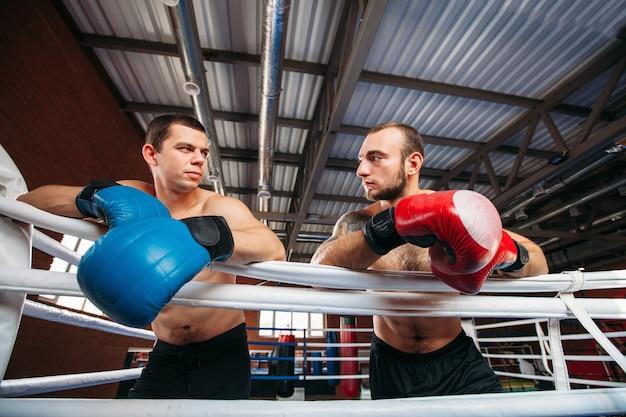 Twee boksers kijken elkaar na de training aan.