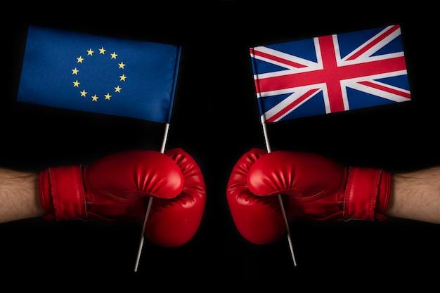 Twee bokshandschoenen met vlag van de europese unie en groot-brittannië. confrontatie en betrekkingen tussen groot-brittannië en de europese unie.