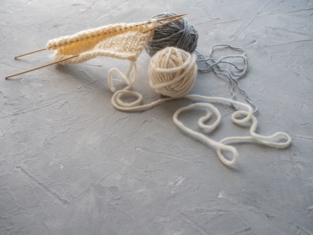 Twee bollen wol en een sjaal breien met houten spaken. het concept van handwerk, handgemaakt.