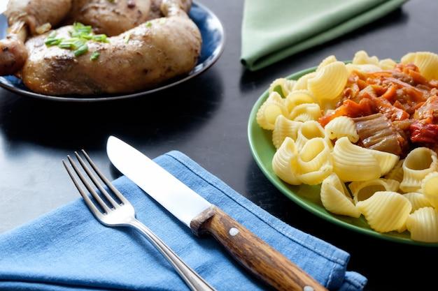 Twee borden met pasta en gebakken kip