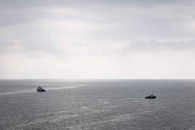 Twee boten varen in verschillende richtingen op de zee op een bewolkte dag