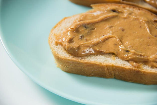 Twee boterhammen met pindakaas in close-up. de boterham met pindakaas ligt op het bord.