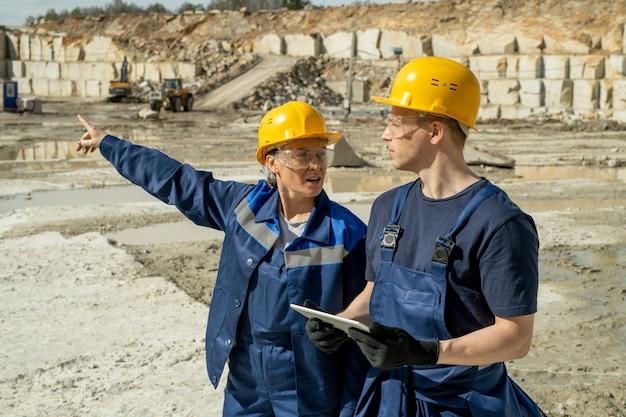 Twee bouwers in werkkleding die discussie hebben op de werkplek