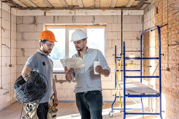 Twee bouwingenieurs praten op de bouwplaats, ingenieur legt een tekening uit aan een werknemer.