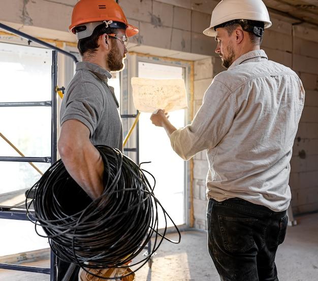 Twee bouwingenieurs praten op de bouwplaats, ingenieur legt een tekening uit aan een werknemer
