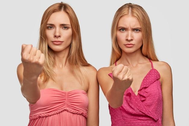 Twee boze blonde vrouwen strekken vuisten, waarschuwen je, dragen roze jurken, zijn ontevreden, gebaren boos