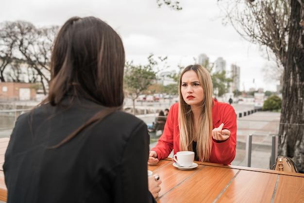 Twee boze vrienden die terwijl het zitten bij koffiewinkel bespreken.