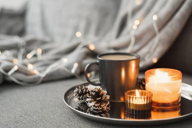Twee brandende aromakaarsen, koffie in een zwarte mok en decoratieve dennenappels