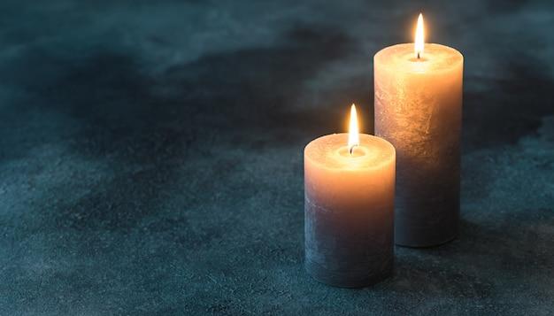 Twee brandende kaarsen op marineblauw oppervlak