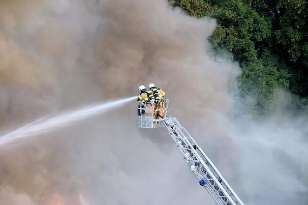 Twee brandweerlieden die de brand in het bos, omgeven door rook, proberen te stoppen