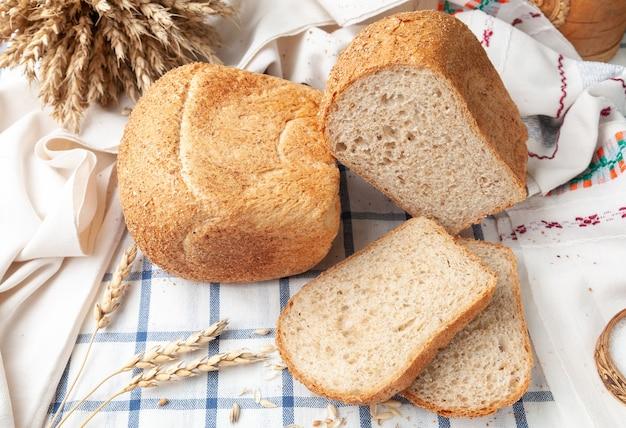 Twee broden van zemelen op een wit blauw gestreept tafelkleed op het tafelkleed liggen twee gesneden sneetjes brood oren van tarwe en graan bovenaanzicht landelijke stijl