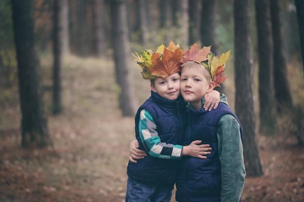 Twee broers die in een bos op de herfstdag knuffelen.