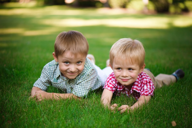 Twee broers die op het gras in een park liggen in openlucht, glimlachen en