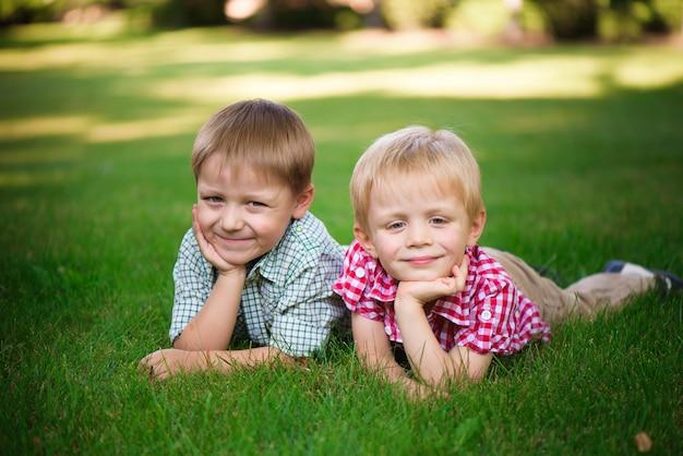 Twee broers die op het gras in een park liggen in openlucht, glimlachend en
