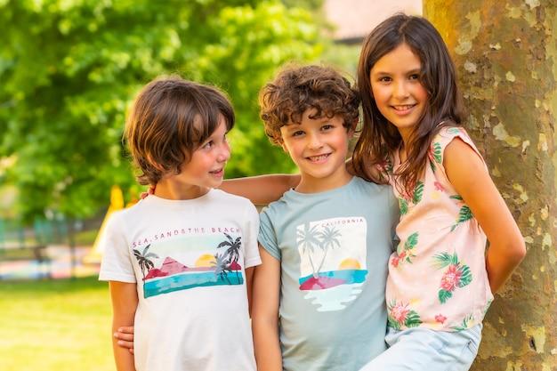 Twee broers en een zus lachend in een park naast een boom