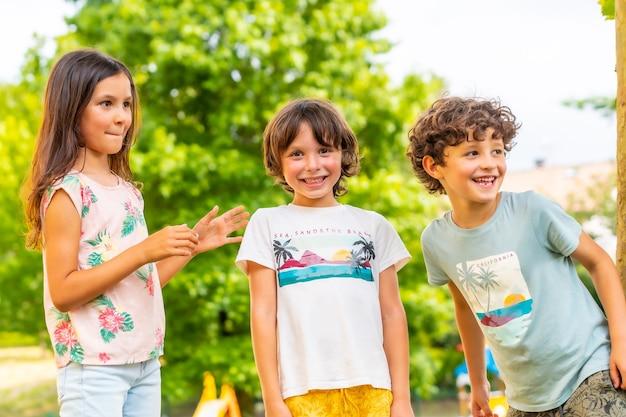 Twee broers en een zus lachend in een park