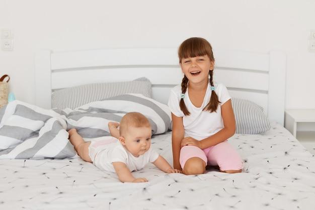 Twee broers en zussen die thuis spelen, poseren op bed, ouder kind dat direct in de camera lacht, donkerharige oudere jongen met een casual stijl spelend met peuterkind dat op de buik ligt.