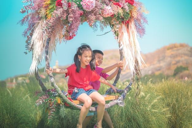 Twee broers en zussen kinderen slingeren op een bloemenschommel