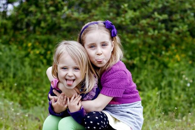 Twee broers en zussen van kleine meisjes laten buiten tongen zien