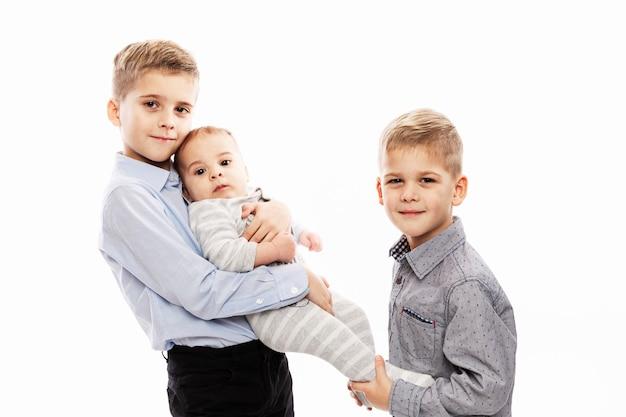 Twee broers houden een pasgeboren baby vast. liefde en tederheid in het gezin.