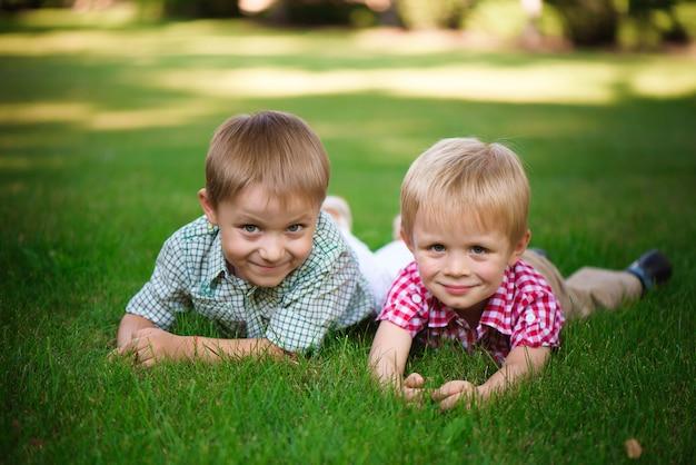 Twee broers liggend op het gras in een park buiten, glimlachend en lachen