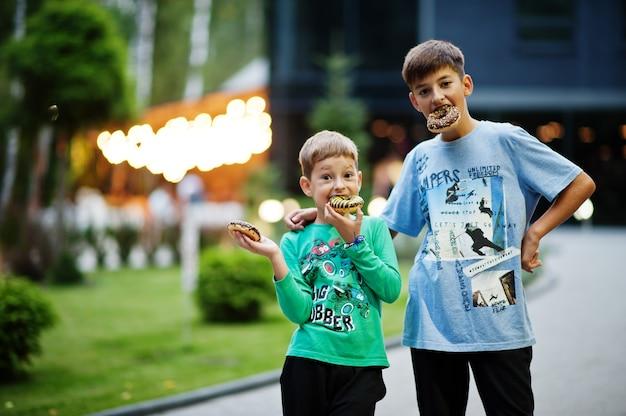 Twee broers met donuts bij avondwerf. lekker lekker donut eten.