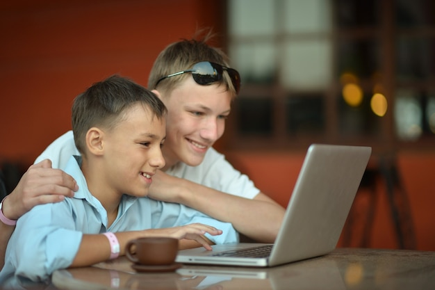 Twee broers met laptop aan tafel in café