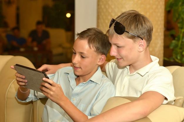 Twee broers met tablet pc in café