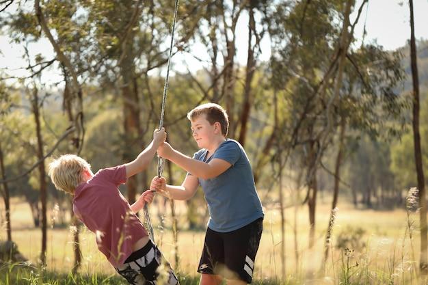 Twee broers spelen op een touwschommel op een prachtige bushlocatie