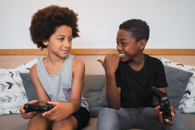 Twee broers spelen videogames thuis.