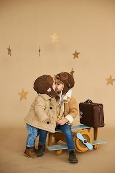 Twee broers worden gespeeld met een speelgoedvliegtuig en een koffer op een beige achtergrond