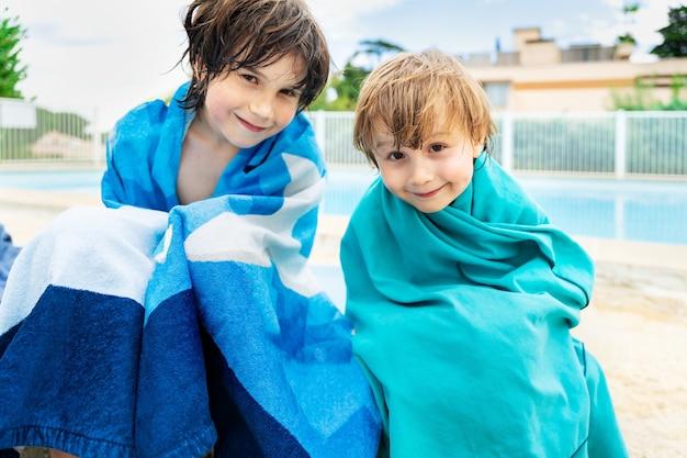 Twee broers zitten bij een zwembad gewikkeld in badhanddoeken na te hebben genoten van water. kinderen brengen zomervakantie samen in familie door.