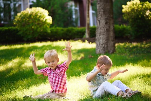 Twee broers zitten op zonnige open plek in park en wachten op vrienden