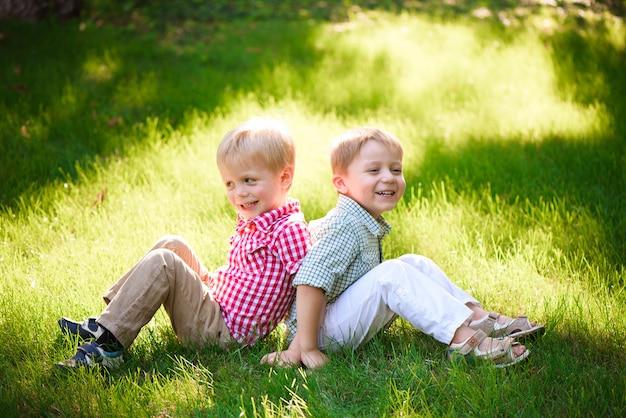Twee broers zitten op zonnige open plek in park