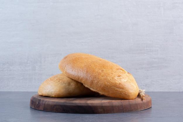 Twee broodjes en een enkele tarwesteel op een houten bord op marmeren achtergrond. hoge kwaliteit foto