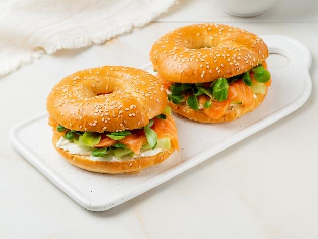 Twee broodjes met zalm, roomkaas, plakjes komkommer op witte marmeren tafel
