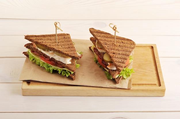 Twee broodjes van driehoekige stukjes brood met kipfilet