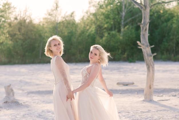 Twee bruiden vrouwen in witte jurk met blond haar knuffelen elkaar, lesbische bruiloft
