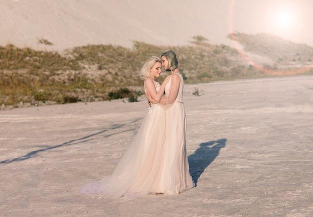 Twee bruidenvrouwen in witte jurk met blond haar knuffelen elkaar, lesbisch huwelijk
