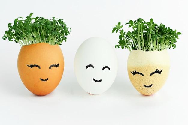 Twee bruine eieren en een witte in het midden met blije gezichten getekend op geïsoleerd op een witte achtergrond