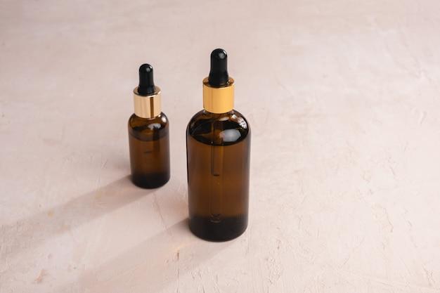 Twee bruine glazen flessen met pipetten geïsoleerd op beige gestructureerde achtergrond