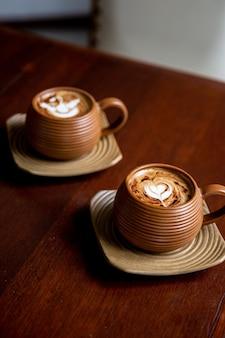 Twee bruine kopjes warme cappuccino op houten tafel achtergrond hartvorm kunst voor symbool van liefde