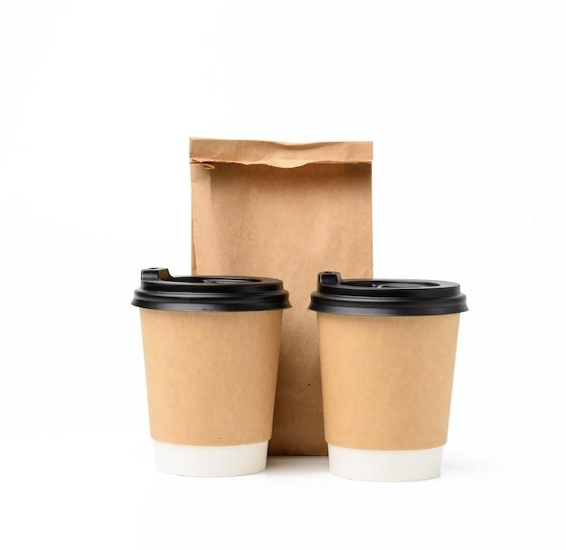 Twee bruine papieren bekers met een plastic deksel en een papieren zak voor voedsel, ecologische recyclebare voedselverpakking op een witte achtergrond