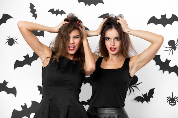 Twee brunette meisjes gekleed in zwarte jurken grimassen op de achtergrond van de muur met vleermuizen. halloween feest. .