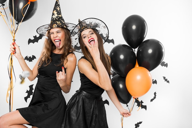Twee brunette meisjes in zwarte jurken en heksenhoeden hebben plezier met ballonnen op de achtergrond van de muur met vleermuizen. halloween.